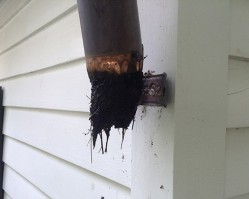 Clogged copper gutter downspout